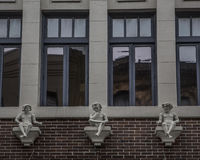 Building Facade and Embellishments. Building facade with windows and embellished with statuettes Royalty Free Stock Photo