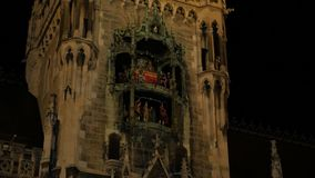 Building Facade With Figures. Dolls statues yellow backlit building tower new city hall neo gothic architecture chapel night scene stock video footage