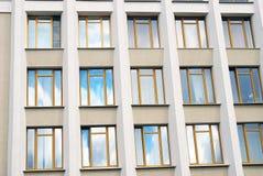 A building facade, glass windows, blue sky reflection. Taken in Russia Stock Photos