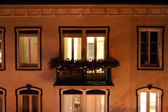 Building facade with illuminated apartment window. Ancient architecture building located in Switzerland, Interlaken, where you can see in detail the exterior of royalty free stock image