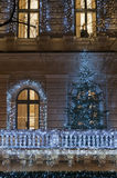 Building facade with light decoration at night with Christmas tr Stock Image
