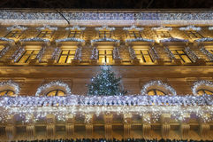 Building facade with light decoration at night with Christmas tr. Building facade with light string decoration at night with Christmas tree on the balcony, door Royalty Free Stock Images