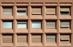 Building facade made of pink granite with large square windows,. Some windows are open, others are closed Stock Photo