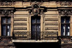 Building facade of old historic house with classic antique arch window and cozy balcony royalty free stock photos