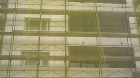 Building facade renovation, old house reconstruction, repair. Scaffold in front of building facade covered with yellow transparent