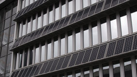 Building Facade With Solar PVs. Building facade with rows of photovoltaic (PV) solar panels mounted between rows of windows. An area of curtain walling to the Royalty Free Stock Image
