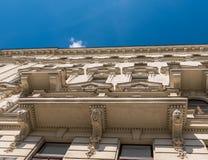 Building facade view towards the sky. Building façade view towards the clear blue sky and one white cloud Stock Photos