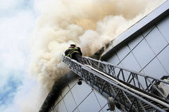 Building on fire. Smoke against the blue sky Stock Photo