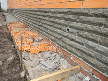 Building foundation waterproofing. New construction waterproofing basement walls from outside with detail of a Stock Image
