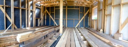 Building the frame of a wooden house. Panoramic picture inside the frame. Boards for flooring, vapor barrier walls. stock image