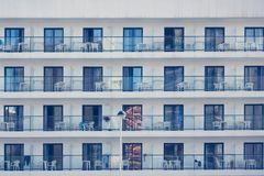 Modern building front wall with repeating pattern of windows and balcony for background. Building front wall with repeating pattern of windows. Horizontal. Close Stock Images