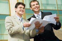 Building the future. Two businesspeople holding papers looking towards and business center with glassy walls on the background Royalty Free Stock Images