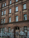 Building with graffiti. Dirty brick buildingl with traces of old graffiti Royalty Free Stock Photo