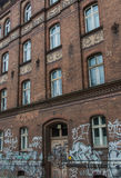 Building with graffiti. Dirty brick buildingl with traces of old graffiti Stock Photography