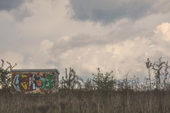 Building with graffiti on a meadow Stock Image
