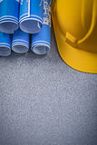 Building helmet blue rolled up construction drawings on grey bac Stock Images
