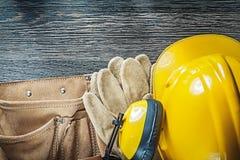 Building helmet earmuffs protective gloves toolbelt on wood boar Stock Image