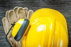 Building helmet earmuffs protective gloves on wood board Royalty Free Stock Photos