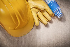 Building helmet protective gloves blue blueprints on wood board Stock Photos