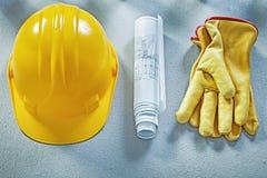 Building helmet protective gloves blueprints on concrete surface Stock Photo