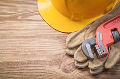 Building helmet protective gloves monkey wrench on wooden board Stock Photos