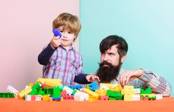 Building home with constructor. little boy with bearded man dad playing together. happy family. leisure time. child. Development. father and son play game royalty free stock photography