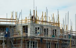 Building a house. Construction workers building a house Royalty Free Stock Image