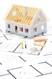 Building house. Building the house concept - model of the house with building material, builder figures and blueprints Royalty Free Stock Photography