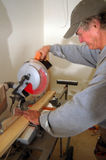 Building the house. A man using saw to saw a board in half Stock Image