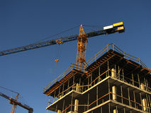 Building a house. Building and two cranes Royalty Free Stock Photos