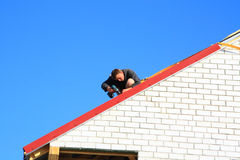 Building a house. A young worker performs work on the roof of the house under construction Royalty Free Stock Photo