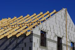 Building a house of wooden planks and gray bricks against a blue sky. Construction of a private house of brown wooden boards and gray bricks against a blue sky stock photo