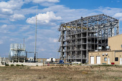 Building at industrial plant. Construction of the industrial building against the cloudy sky Stock Images
