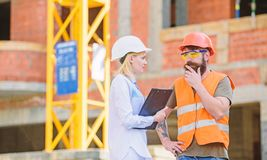 Building industrial project. Construction industry concept. Discuss progress project. Woman engineer and bearded brutal stock images