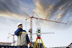Building industry and suveying engineer. Construction engineer surveying with measuring instrument, cranes and industry in background Stock Image