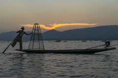 Fisherman on the Inle lake in Myanmar. A leg rowing fisherman on Inle Lake in Shan State in Myanmar (Burma).This unique style of rowing evolved because the Royalty Free Stock Images