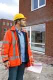Building inspector. A building inspector visiting a construction site with a checklist in his hand Royalty Free Stock Photography