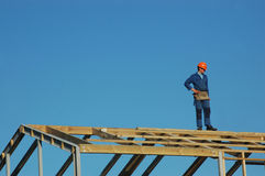 Building inspector. Builder standing on top of roofing framework Royalty Free Stock Photography