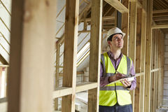 Building Inspector Looking At New Property. Building Inspector With Clipboard Looking At New Property Royalty Free Stock Photo