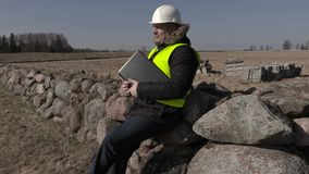 Building inspector sitting on stone fence and using laptop stock video footage