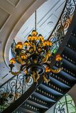 Architecture interior, candelabra and curved staircase viewed from below. Building interior detail, spiral staircase, ceiling and chandelier Royalty Free Stock Photo