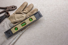 Building level with glove and tool. Royalty Free Stock Photography