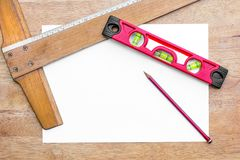 Building level, T square ruler and pencil with a piece of white paper on a table background. Texture royalty free stock photos