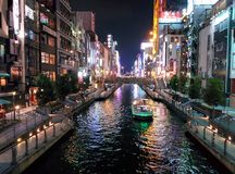Building lights reflect off the Dotonbori Canal in Osaka, Japan. Stock Photos
