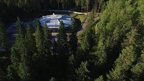 Building like UFO in a forest. Aerial stock video footage