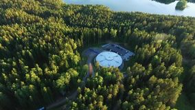 Building like UFO in a forest. Aerial stock footage