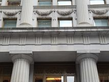 Facade of historic stone building with architectural detail of columns and ornate windows stock image