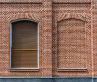 The building is made of brick in loft style. Window with blinds and a window laid with brick. stock photo