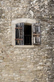 Building made of natural stone with a window and half-open shutt Stock Photo