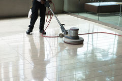 Building Maintenance, Cleaning, Floor Polishing. A worker is polishing a tile floor to make it shine and clean. The worker uses a polisher machine to get the job royalty free stock photos